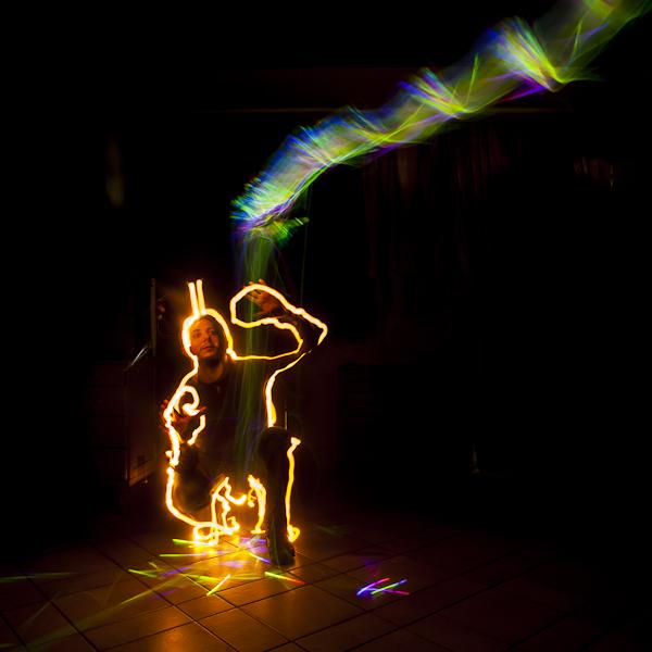 Un type assis par terre, entouré à la lampe torche, faisant mine de recevoir une comète dessinée avec des batonnets lumineux
